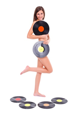 Nude girl standing with vinyl discs in her hand, white background  photo