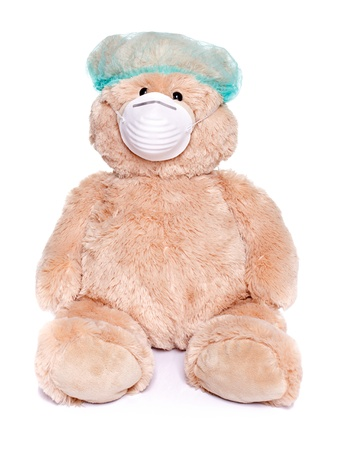 Teddy bear sitting with medical mask and cap over white background  photo