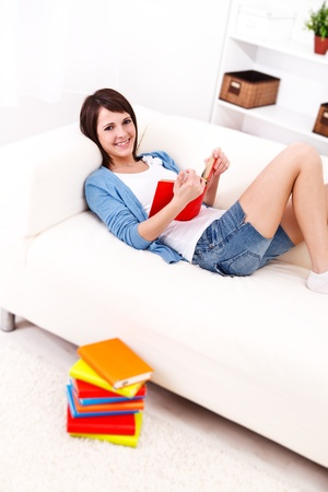 Lovely girl on the sofa reading books
