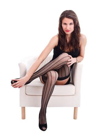 Attractive woman in erotic underwear sitting in armchair, studio shot Stock Photo - 16639301