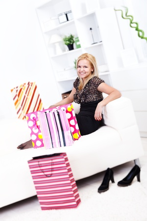 Pretty woman with bags on the sofa after shopping