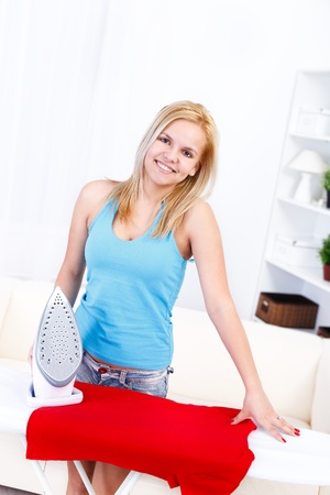 Pretty housewife ironing a red dress  photo
