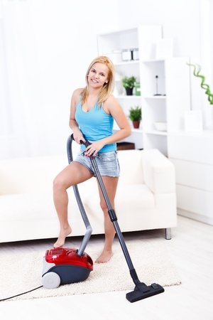 Pretty young woman using vacuum cleaner at home