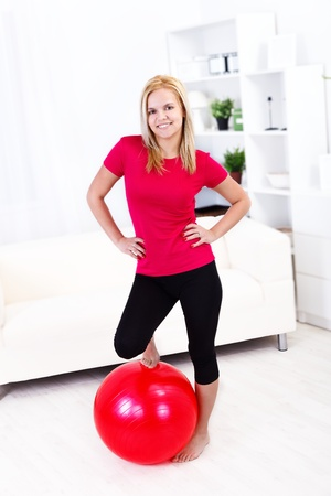 Sexy fitness girl with red pilates ball at home