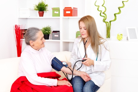 Elderly woman has her blood pressure checked by the nurse   Stock Photo