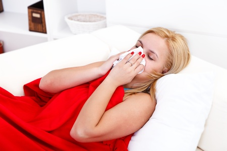 Sick woman lying in bed blowing her nose Stock Photo - 16890987