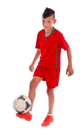 Young kid in red uniform  playing football - studio shot  photo
