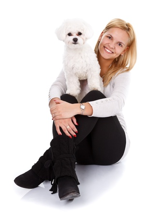 bichon bolognese: Cute young girl with her bichon bolognese dog looking to the camera