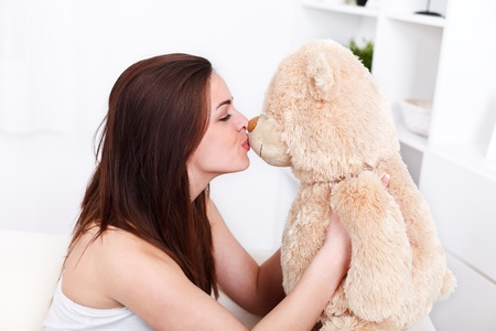 Young woman sitting in sofa kissing her lovely teddy bear  photo