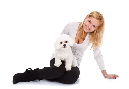 bichon bolognese: Young blonde beauty sitting on the floor with a little puppy over white background