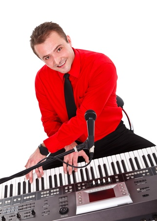 Smiling singer playing electric synthesizer over white background  photo
