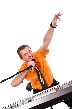 Joyful young man posing with microphone and synthesizer  over white background