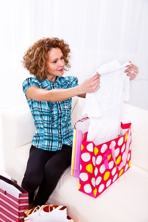 shoppingbags: Attractive young woman in her home after a day of shopping, looking at the clothes she bought