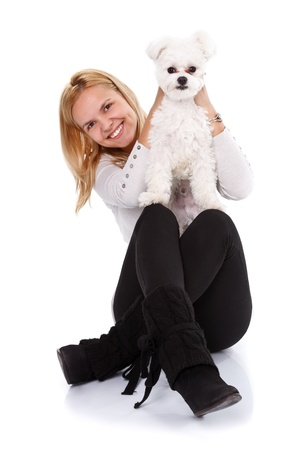 bichon bolognese: Young happy woman showing to camera a cute small bichon bolognese dog