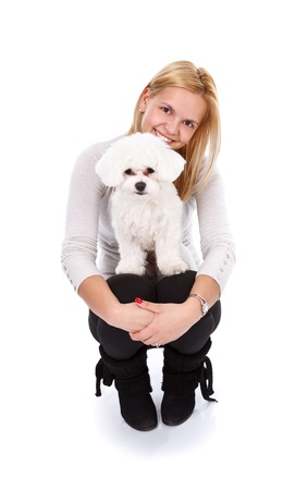 bichon bolognese: Portrait of a young blonde girl with a cute white puppy - studio shot  Stock Photo