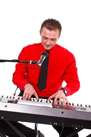 Synthesizer artist in red shirt playing on keyboard behind microphone  photo
