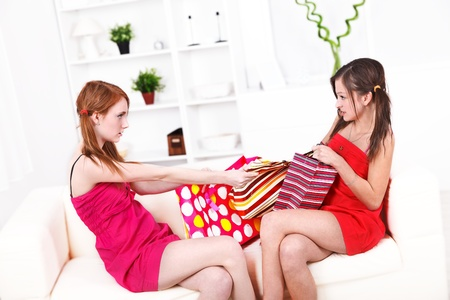 shoppingbags: Two girls fighting for shopping bags, pulling them.  Stock Photo