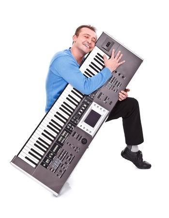 passionately: Young man passionately embraces his sythesizer - studio shot