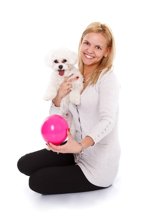 bichon bolognese: Smiling young woman holding a small white puppy and a small pink ball - studio shot