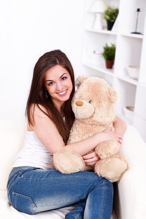Girl sitting on sofa holding her lovely big teddy bear in hand  photo