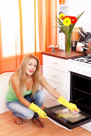 Beautiful young housewife cleaning the oven with sponge after baking a cake in it. Stock Photo - 18327187
