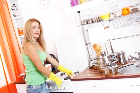 Beautiful young woman cleans the oven in the kitchen, wearing yellow gloves 