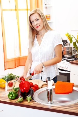 Beautiful blonde woman cutting vegetables in the kitchen