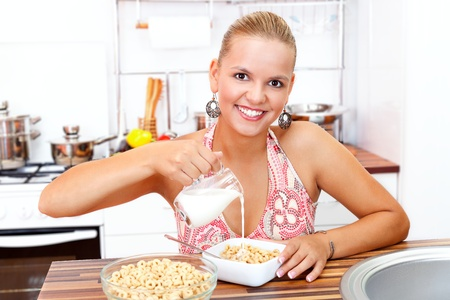 Young woman eating her healthy breakfast in the kitchen Stock Photo - 18327141