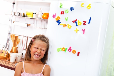 Little girl making funny face in front of the fridge with color letter magnets on it  Stock Photo