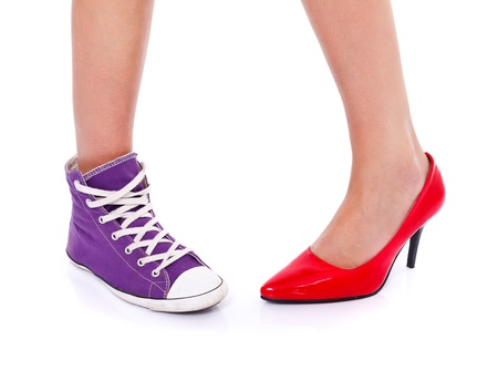 Woman wearing red high heel shoe on one leg and sport shoe on another leg