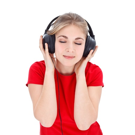 Nice girl in red t-shirt relaxing by listening music with headphones over white background photo