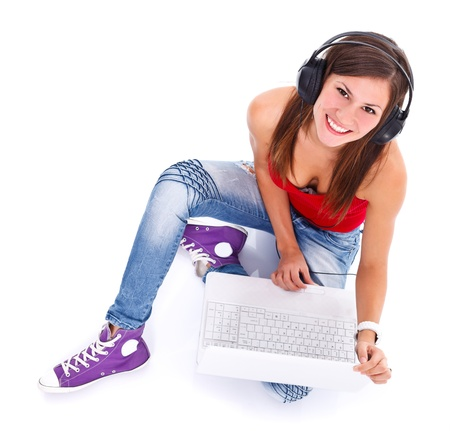 Portrait of a cute young smiling woman with headphones and notebook photographed from above. Studio shot.  Stock Photo