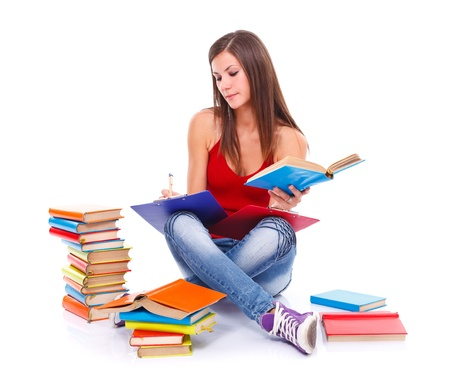 Young student woman sitting on the floor surrounded with books, taking notes, preparing for exam. White background.  photo
