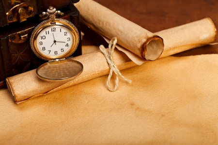 A desk with treasure box, old paper rolls and pocket watch with open lid.  photo