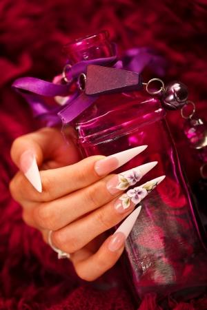 elixir: La mano de una mujer con las u�as artificiales holdig una botella de elixir de belleza
