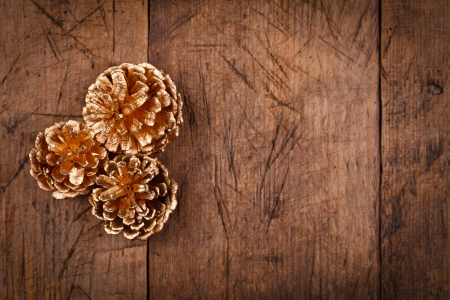 pine three: Above view of three golden pine cones on wooden table background.  Stock Photo
