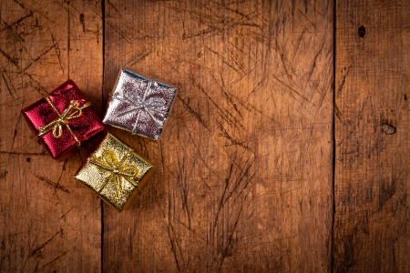 Three small Christmas present box on vintage wooden background. Above view.  photo