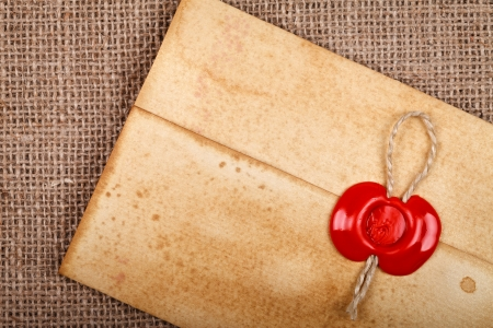 burlap background: Detail of old grunge envelope with red wax seal on hessian sacking burlap background.  Stock Photo