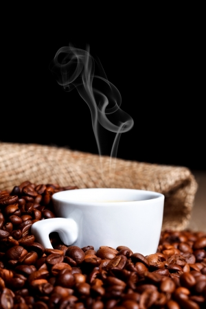 steamy: White steamy cup among coffee beans with burlap  Stock Photo