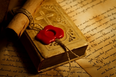 Closeup view of old prayer book with ancient paper roll with wax seal, old letters in background  Stock Photo