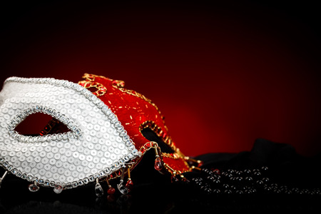 peal: Black peal near white and red carnival masks Stock Photo