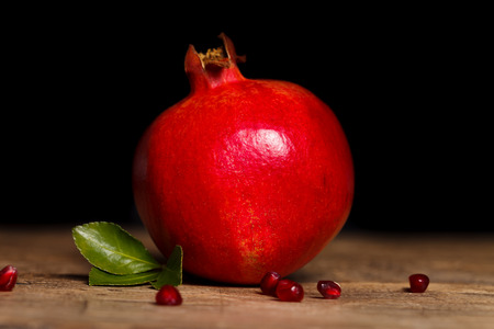 grenadine: Red grenadine on the table with small seeds and a green leaf