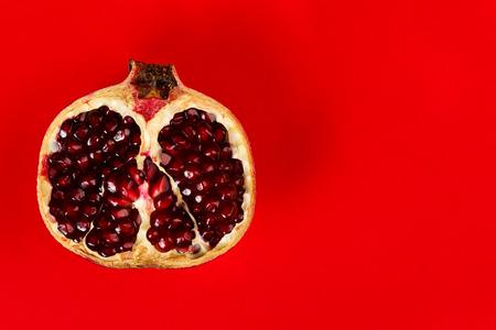 grenadine: Half grenadine on the left side over red background Stock Photo