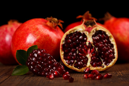 grenadine: Grenadine fruits and seeds with small green leaf on rustic wooden table