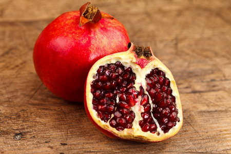 grenadine: A whole and a half grenadine on a rustic wooden table