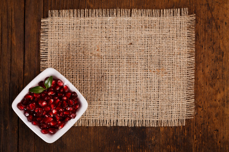 grenadine: Grenadine seeds in white plate on canvas, wooden background, upper view