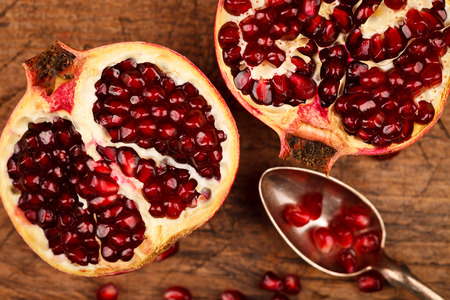 grenadine: Upper view of grenadine fruits and seeds with silver teaspoon, rustic background