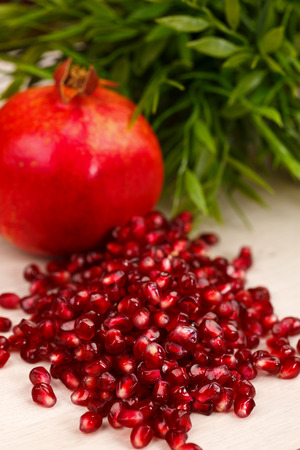 grenadine: Heap of grenadine seeds with fruit and green leaves in the back