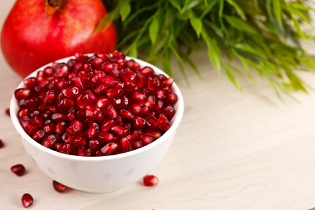 grenadine: Grenadine seeds in a plate with fruit and green leaves in the back