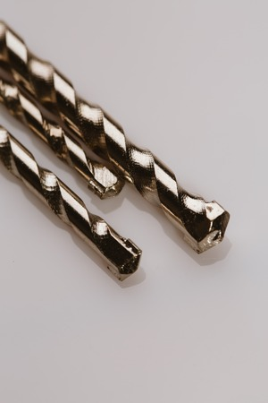 Drill bits of different sizes over white background.